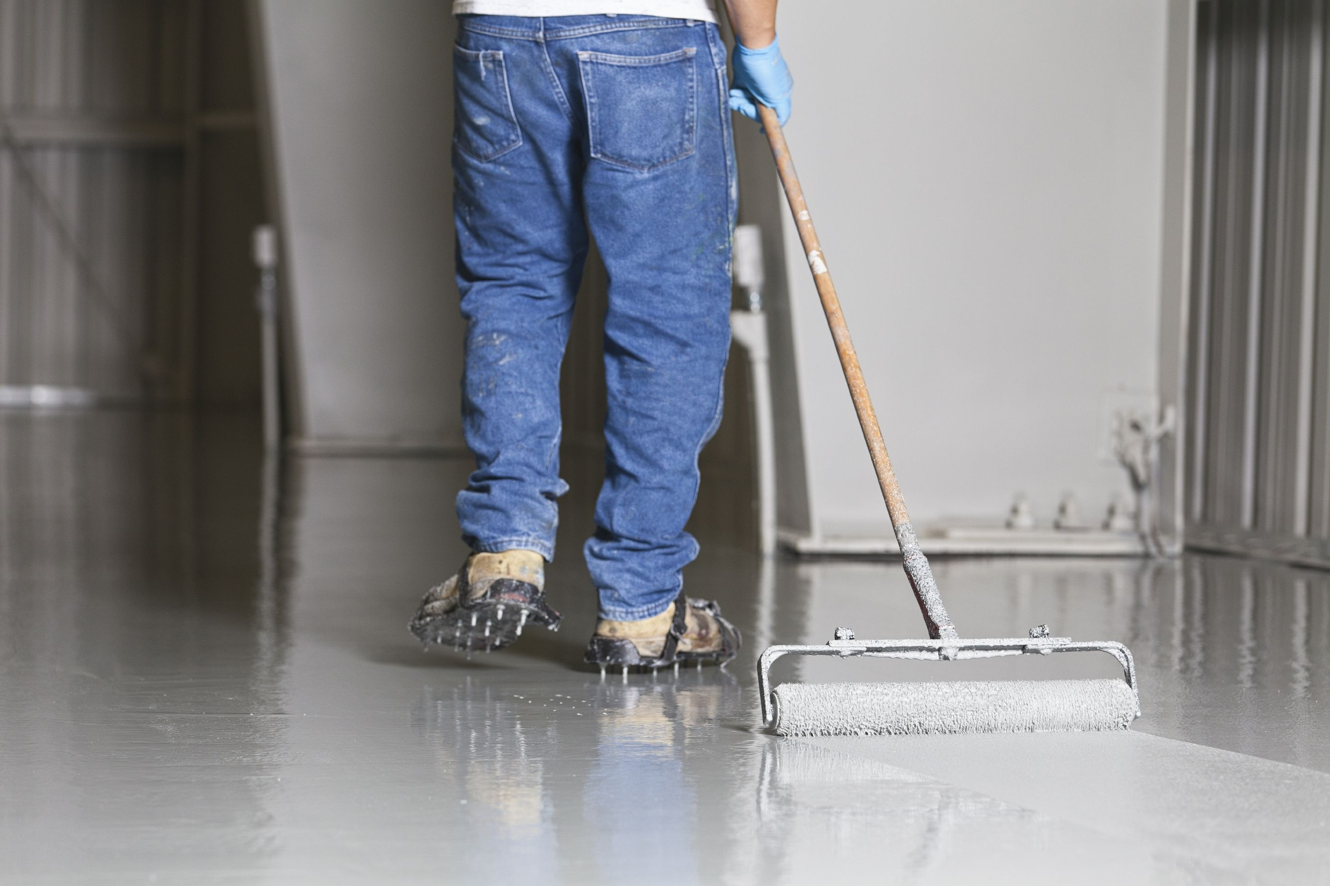 primer being applied to concrete floor