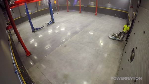 QuestMark employee polishing concrete floor in auto garage