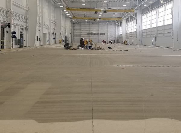concrete floor of a hangar gets prepared for epoxy flooring