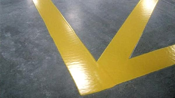 close up of yellow safety lines on concrete floor