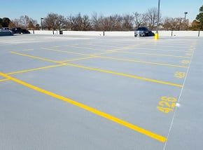 gray coated parking deck with yellow lines