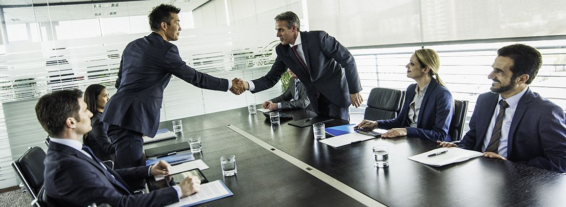 two men shake hands across meeting room table