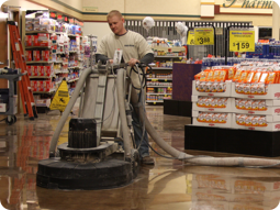 QuestMark employee operates concrete floor polisher in grocery store