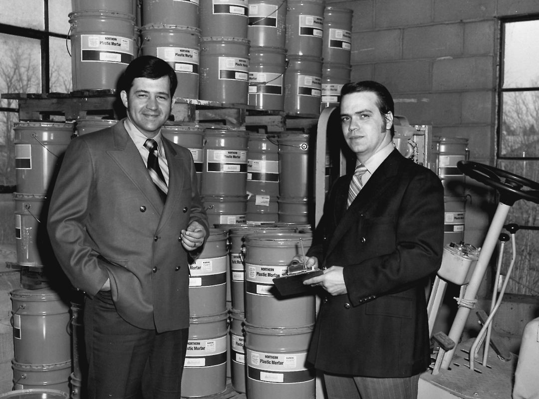 black and white photo of two men with stacked five gallon buckets